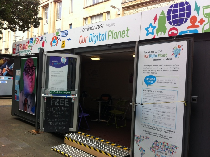 Internet Station - a portbale room with signs on the ourside say9ng our digital planet and images of people using digital equipment